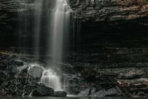 Waterfall Rains Down To The Rocks Below Photo