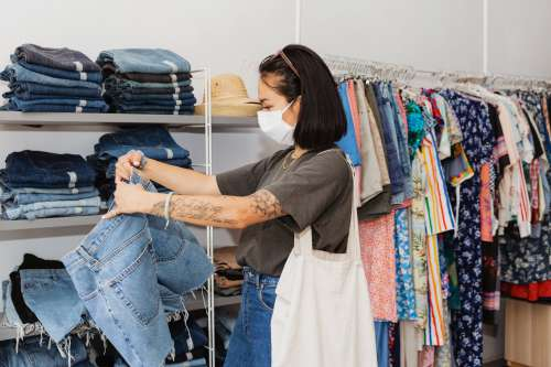 Young Woman Shopping For Clothes With Face Mask On Photo
