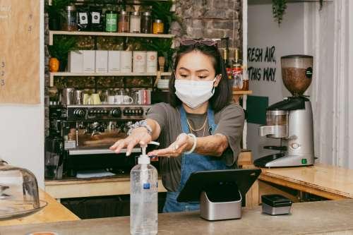 Retail Staff Sanitizing Her Hands Photo