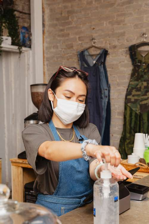 Woman In Retail Store Sanitizing Her Hands Photo