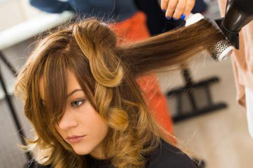 Beauty, hairstyle. Hairdresser curling hair