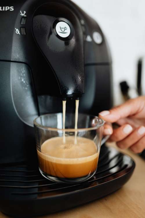 The woman makes coffee with the machine