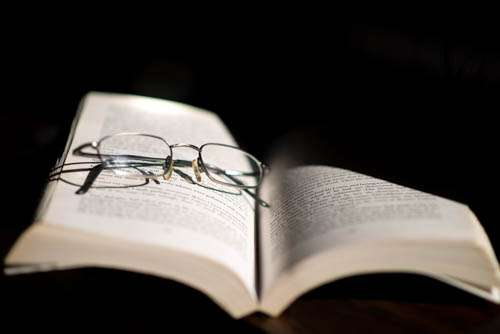 Reading Glasses Resting On Open Book