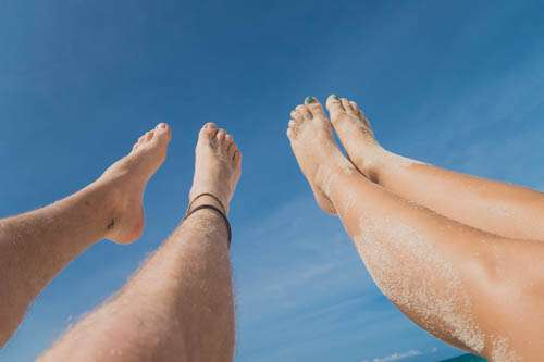 Feet of Man And Girl In The Air With Blue Sky