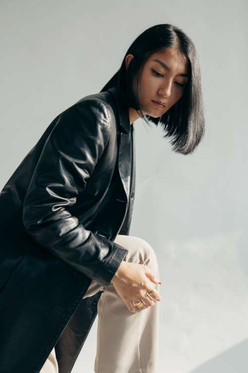Model Wearing Leather Jacket And Tan Pants Photo