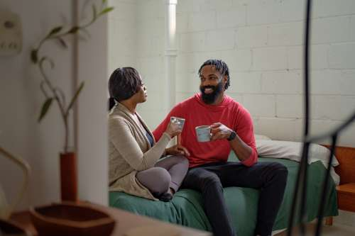 Couple Sip Coffee On The Bed Photo