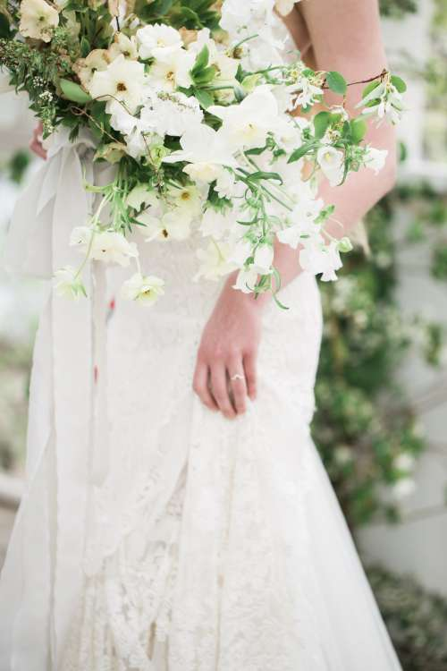 A Brides Dress And Bouquet Of Flowers Photo