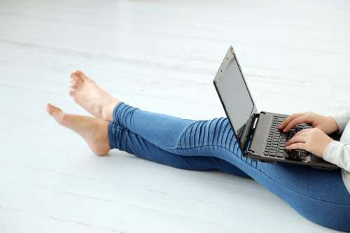 Girl on the ground with a laptop, typing away