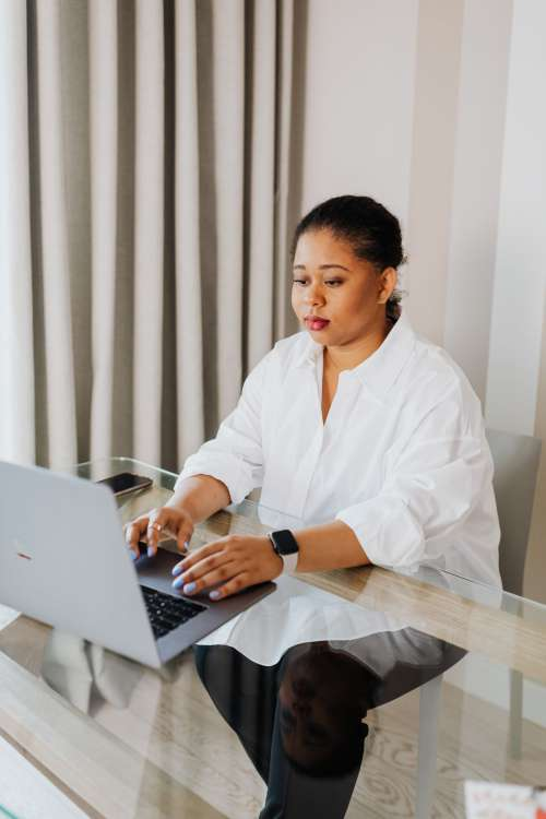 A young woman works on a laptop from home
