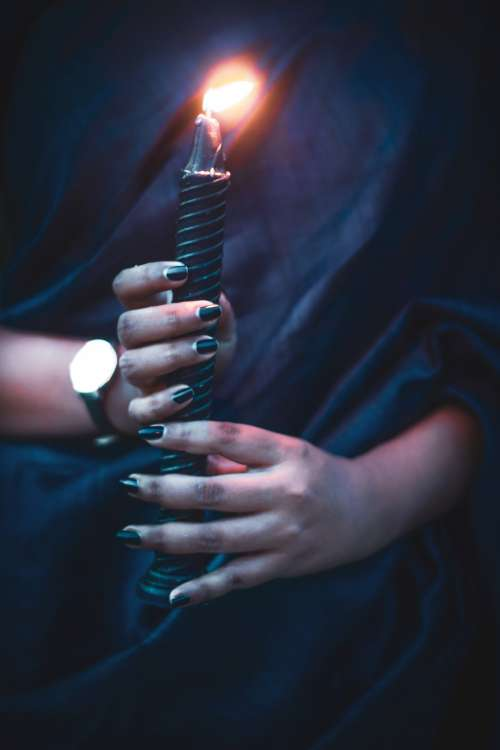 Two Hands Hold Black Candle Photo