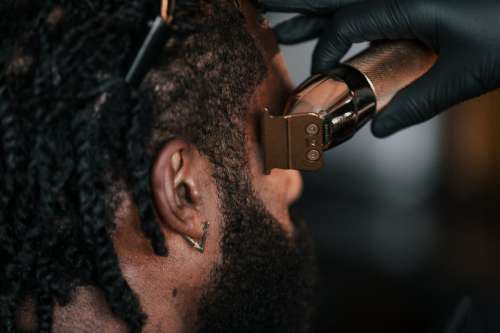 Close Up Of Barber Cutting Hair With Clippers Photo