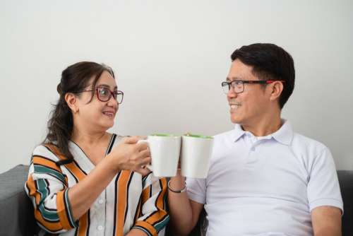 Two People Cheers With Coffee Cups Photo