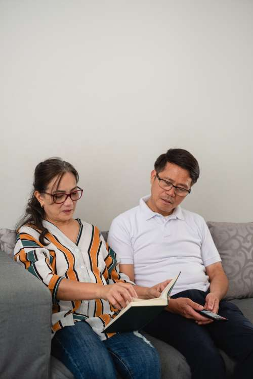 Woman Reading A Book While Man Looks Over Photo
