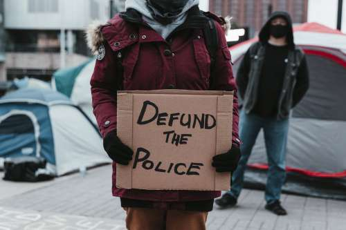 Person Holds Cardboard Sign In Protest Photo