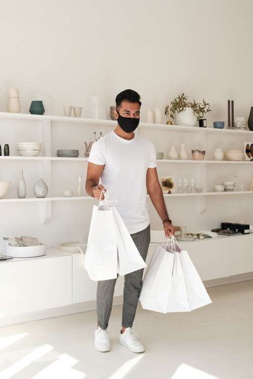 Customer In Face Mask Smiles And Holds White Shopping Bags Photo