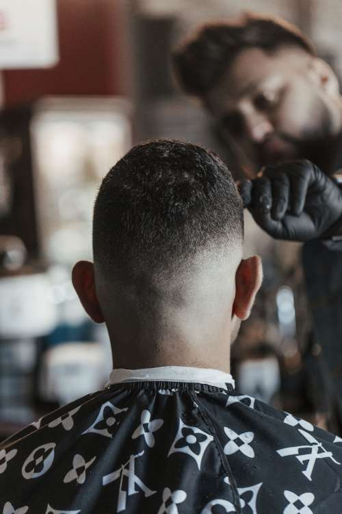 Barber Inspects His Work Of A Clean Haircut Photo