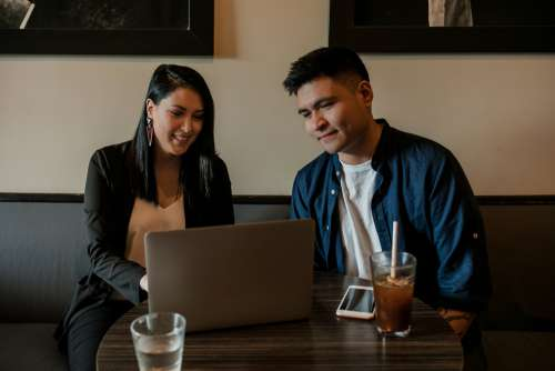Young Man And Woman At Table In Coffee Shop Photo