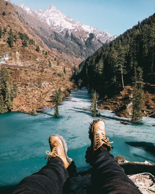 Hiking Shoes Reach Out To A Cold Aqua Lake And Rocky Mountians Photo