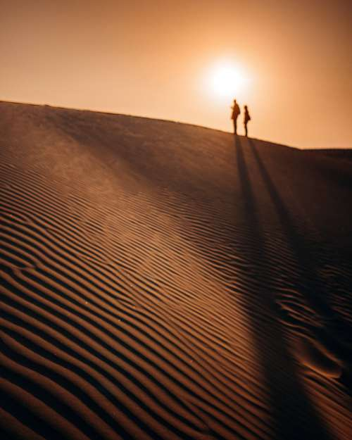 Silhouettes Of People At The Top Of A Sand Dune Photo