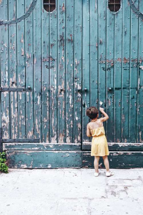 Young Person Knocks On Large Blue Doorway Photo