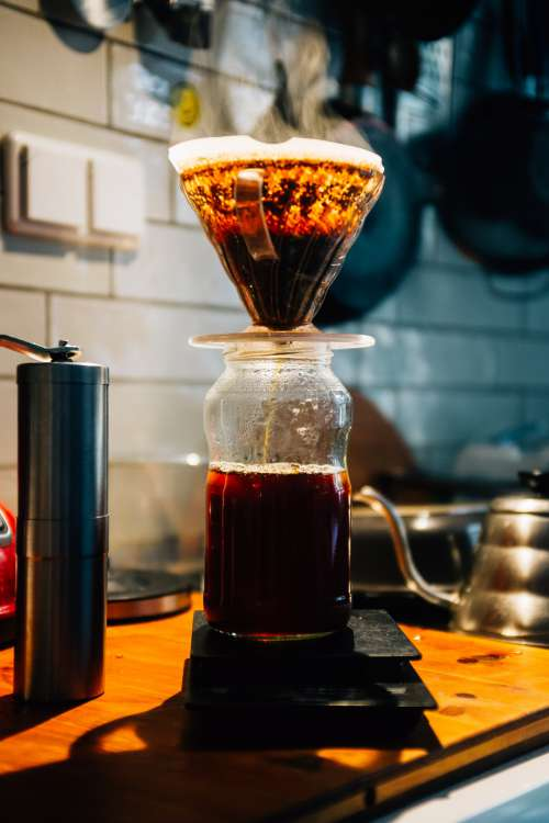 Glass Pour Over Coffee Being Brewed On Wooden Countertop Photo