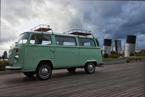 Vintage Teal Camper Van Parked On A Wooden Walkway Photo