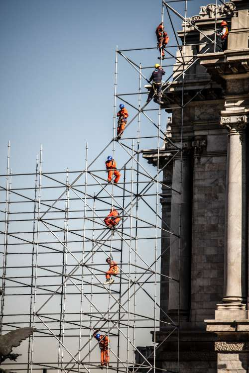 People In Orange Jumpsuits On Tall Scaffolding Photo