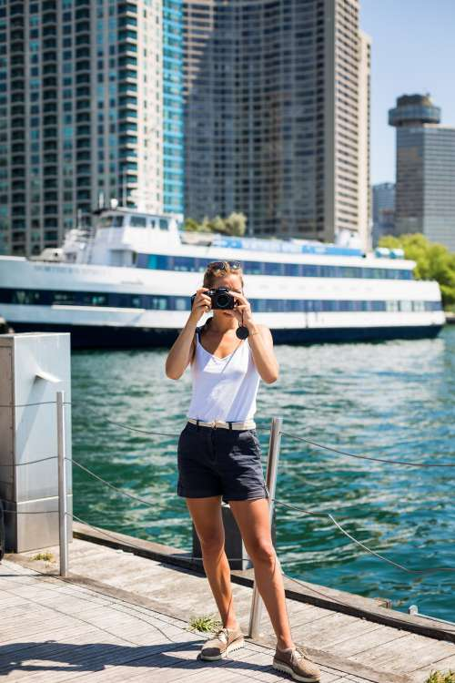 Person Stands By Waterfront And Holds Camera Up To Take A Picture Photo
