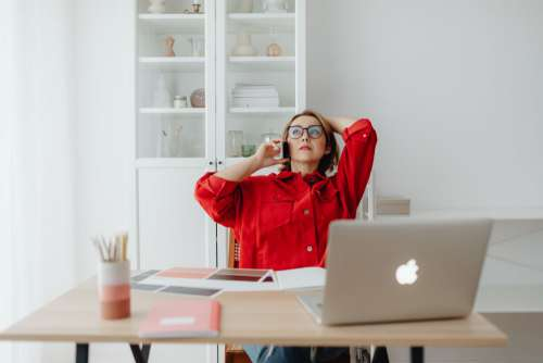 A woman works at a desk in her home