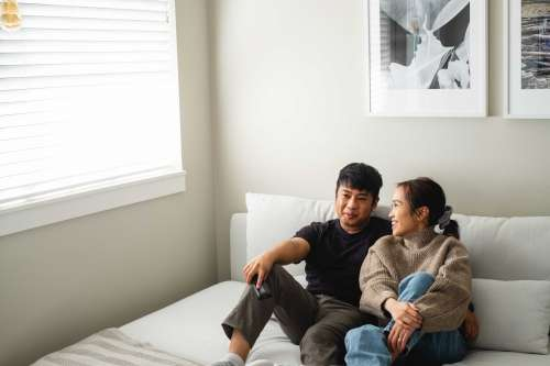 A Couple Relax On A White Couch In Their Living Room Photo