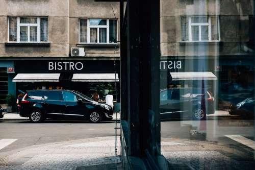 A Black Car Parked Outside A Bistro Photo