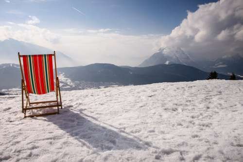 The Back Of A Beach Chair Looking Out To Snow Covered Mountains Photo