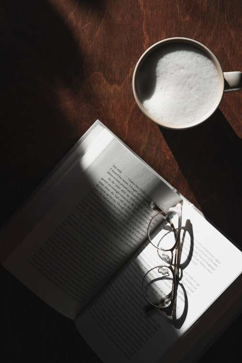 Wooden Table With Latte And Open Book With Glasses Photo