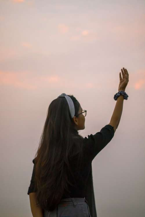 A Person With Long Hair Holding Arm Up To The Sky Photo