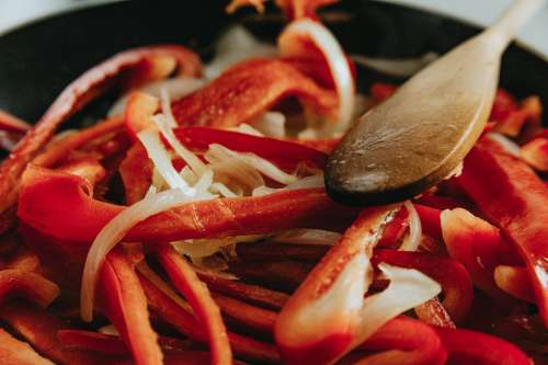 Close Up Of White Onions And Red Peppers Cooking In A Pan Photo