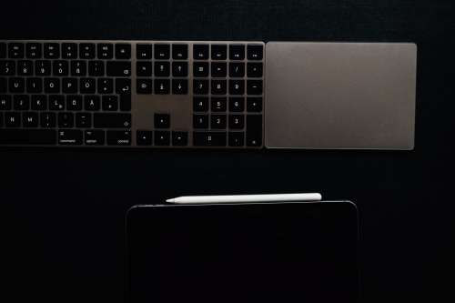 A Keyboard And Tablet On A Black Surface Photo