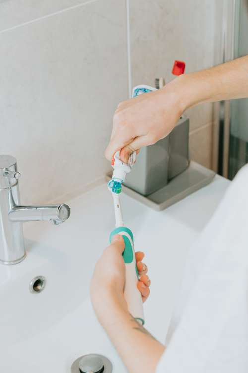 Hands Adding Toothpaste To An Electric Toothbrush Photo