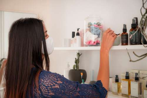 Person In White Facemask Browses Products Photo