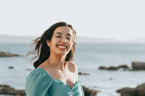 Woman In Glasses Smiles By The Rocky Shoreline Photo