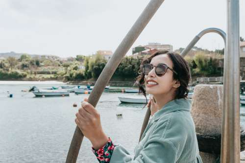 Woman In Sunglasses Smile For The Camera With Boats Below Photo