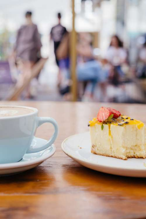 Latte and a cheesecake on a café table 4