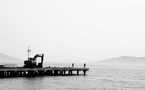 Black And White Photo Of A Dock On Calm Water Photo